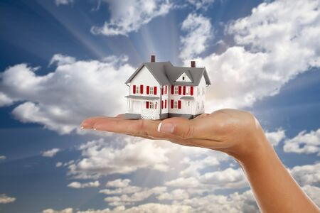 Model House in Female Hand on a Cloud and Sky Background. photo