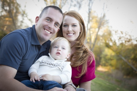 Young Attractive Parents and Child Portrait Outdoors at a Park. photo