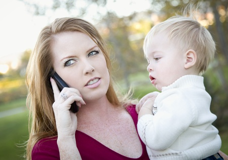 Stressed Attractive Woman Using Cell Phone with Child in Arms. photo