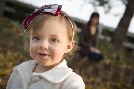 Adorable Baby Girl Playing Outside in the Park with Mom Behind Her. Stock Photo - 11641946