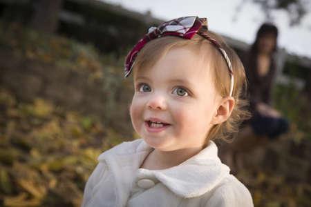 niños jugando en el parque: Niña adorable que juega afuera en el parque con mamá detrás de ella. Foto de archivo