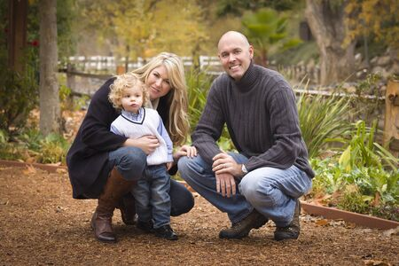 Young Attractive Parents and Child Portrait Outside in the Park. photo