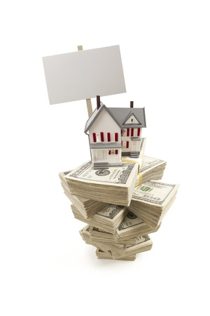 Small House on Stacks of Hundred Dollar Bills and Blank Sign Isolated on a White Background. photo