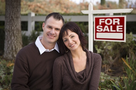 Happy Attractive Caucasian Couple in Front of Real Estate Sign. photo