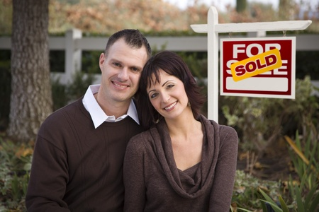 sold: Happy Attractive Caucasian Couple in Front of Sold Real Estate Sign. Stock Photo