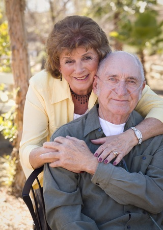 living together: Senior Woman Outside with Seated Man Wearing Oxygen Tubes.