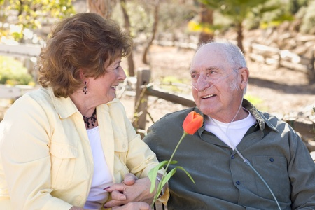 assisted living: Senior Woman Outside with Seated Man Wearing Oxygen Tubes.
