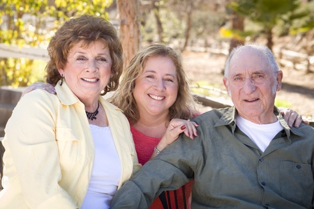 Portrait of Senior Couple with Daughter in the Park. photo