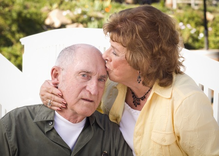 Happy Senior Couple Kissing in the Park. photo