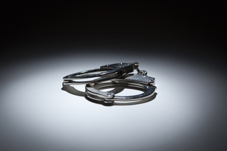 shackle: Abstract Pair of Handcuffs Under Spot Light on Gradated Background.