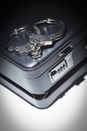 Pair of Handcuffs and Briefcase Under Spot Light Abstract. Stock Photo - 12511598