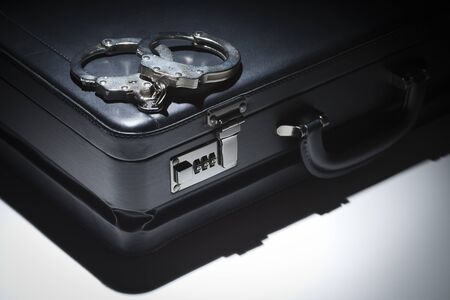 Pair of Handcuffs and Briefcase Under Spot Light Abstract. Stock Photo - 12511596