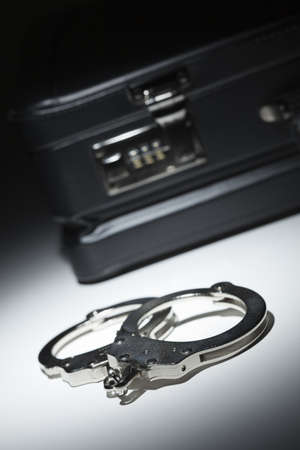 Pair of Handcuffs and Briefcase Under Spot Light Abstract. photo
