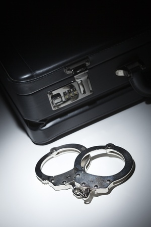 Pair of Handcuffs and Briefcase Under Spot Light Abstract. Stock Photo - 12511594
