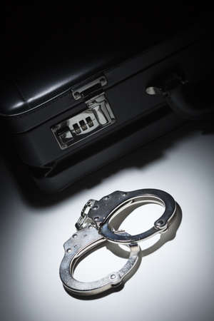 Pair of Handcuffs and Briefcase Under Spot Light Abstract. Stock Photo - 12511608