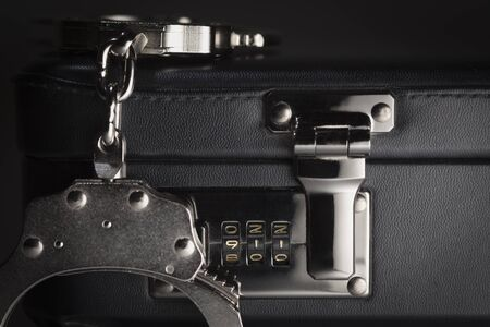 Pair of Handcuffs on Briefcase with the Numbers 911 on Lock. photo