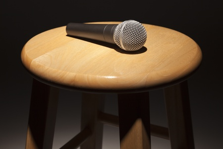 stool: Microphone Laying on Wooden Stool Under Spotlight Abstract.