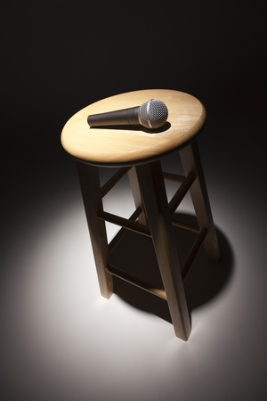 escabeau: Microphone Couch� sur un tabouret de bois sous R�sum� Spotlight. Banque d'images
