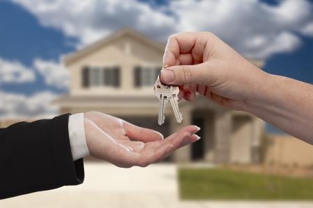 home key: Entrega de las llaves de casa en frente de una casa nueva y hermosa. Foto de archivo