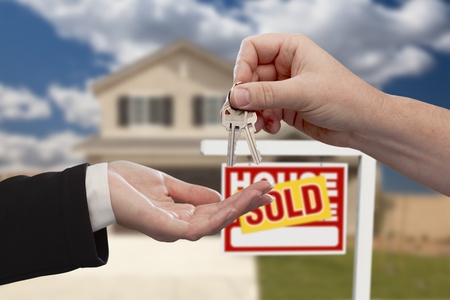 Handing Over the House Keys in Front of Real Estate Sign and Sold New Home. photo