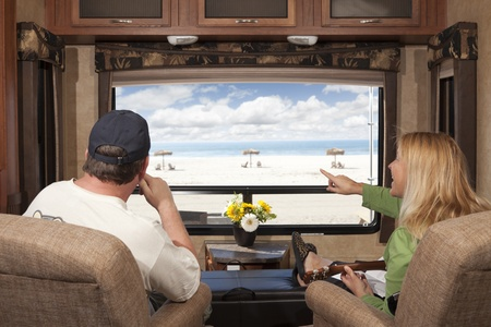 rv: Young Couple Enjoying the Beach View From Their 5th Wheel RV.