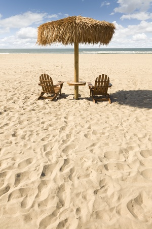 adirondack chair: Two Beach Chairs and Umbrella on a Beautiful Ocean Front with Copy Space. Stock Photo