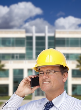 Handsome Contractor in Hardhat and Necktie Smiles as He Talks on His Cell Phone in Front of Building. Stock Photo