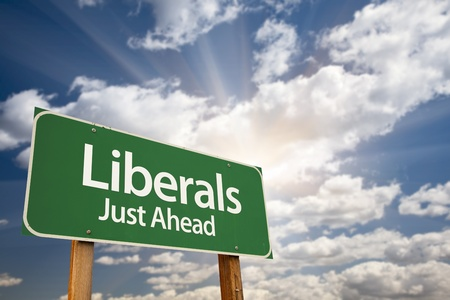 libertarian: Liberals Green Road Sign with Dramatic Clouds, Sun Rays and Sky.