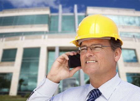 hard look: Handsome Contractor in Hardhat and Necktie Smiles as He Talks on His Cell Phone in Front of Building. Stock Photo