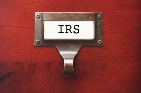 Lustrous Wooden Cabinet with I.R.S. File Label in Dramatic LIght. Stock Photo - 12837796
