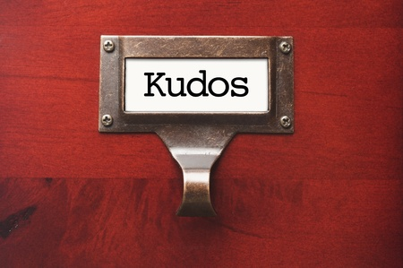 kudos: Lustrous Wooden Cabinet with Kudos File Label in Dramatic LIght. Stock Photo