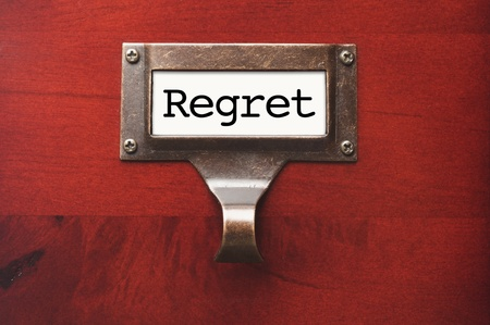 regret: Lustrous Wooden Cabinet with Regret File Label in Dramatic LIght. Stock Photo