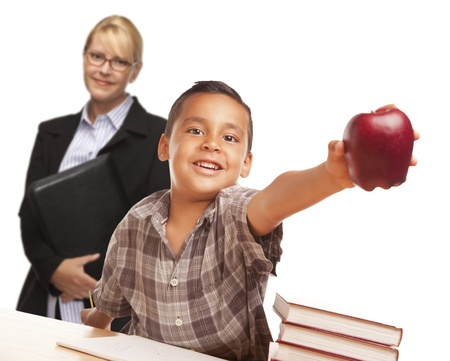 giving back: Hispanic Student Boy At Desk with Apple and Female Adult Behind.