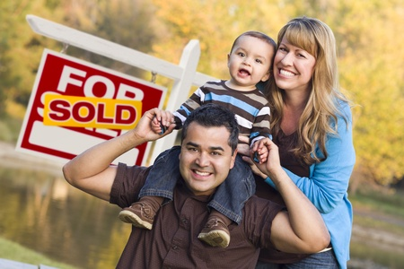 Happy Mixed Race Couple with Baby in Front of Sold Real Estate Sign. Stock Photo - 12837960