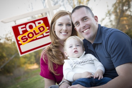 Happy Young Caucasian Family in Front of Sold Real Estate Sign. Stock Photo