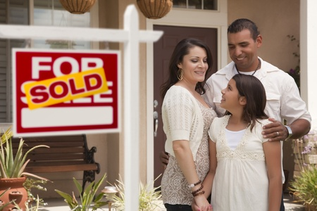 Hispanic Mother, Father and Daughter in Front of Their New Home with Sold Home For Sale Real Estate Sign. Stock Photo - 12837957