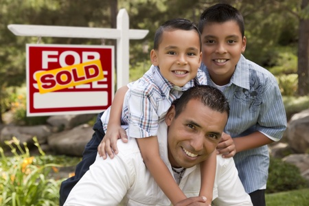 Hispanic Father and Sons in Front of a Sold Home For Sale Real Estate Sign. photo