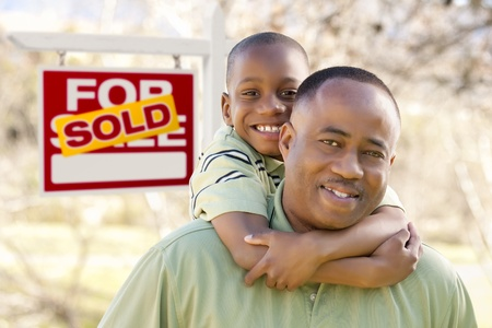 Happy African American Father and Son in Front of Sold Real Estate Sign. photo