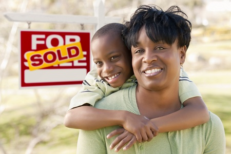 Happy African American Mother and Child In Front of Sold Real Estate Sign. photo