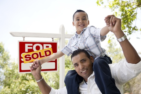 for sale: Excited Hispanic Father and Son in Front of Sold For Sale Real Estate Sign. Stock Photo