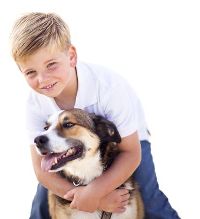 ni�os rubios: Chico guapo joven jugando con su perro aislado en un fondo blanco. Foto de archivo