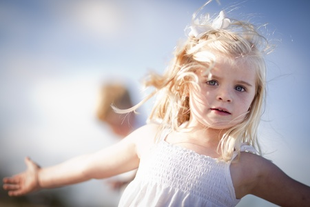 twirling: Adorable Blue Eyed Girl Playing Outside with Her Family. Stock Photo