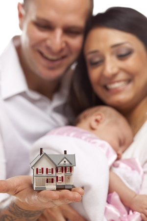 Young Attractive Happy Mixed Race Family with Baby and Small Model House. Stock Photo - 13030692