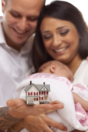 Young Attractive Happy Mixed Race Family with Baby and Small Model House. photo