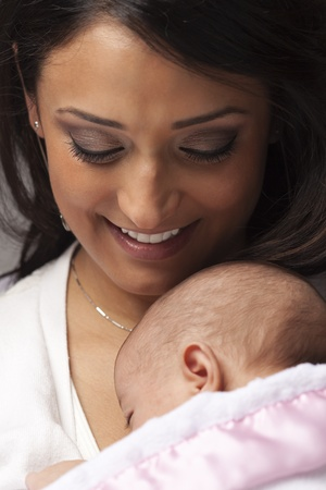 Young Attractive Ethnic Woman Holding Her Newborn Baby Under Dramatic Lighting. Stock Photo - 13030696