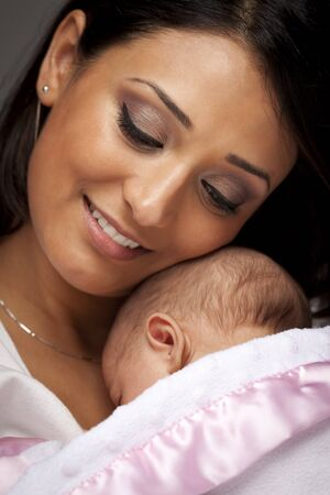 Young Attractive Ethnic Woman Holding Her Newborn Baby Under Dramatic Lighting. Stock Photo - 13030691