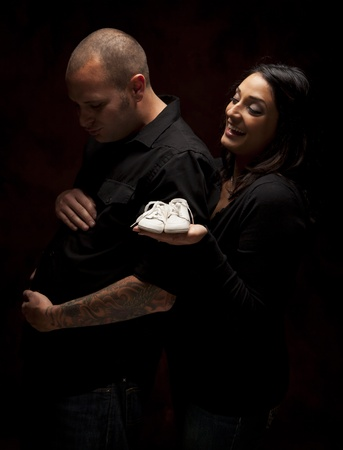 Fun Mixed Race Couple Holding New White Baby Shoes Against a Black Background Under Dramatic Lighting. photo