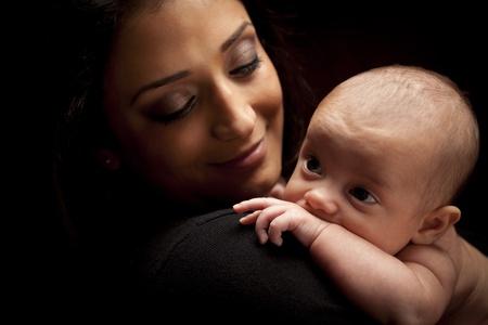 adultbaby: Junge Attraktive Ethnische Frau mit ihrem Neugeborenen unter dramatischen Beleuchtung.