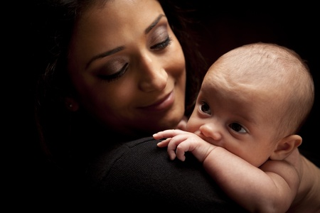 infant hand: Young Attractive Ethnic Woman Holding Her Newborn Baby Under Dramatic Lighting.