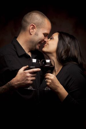 Happy Young Mixed Race Couple Holding Wine Glasses Against A Black Background. photo